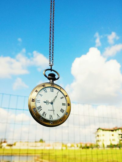 Close-up of antique pocket watch against sky