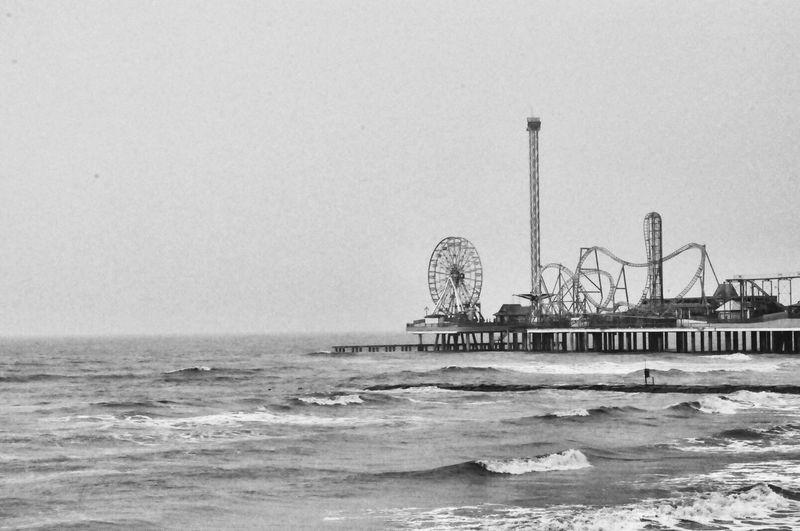 Amusement Park By Sea Against Clear Sky