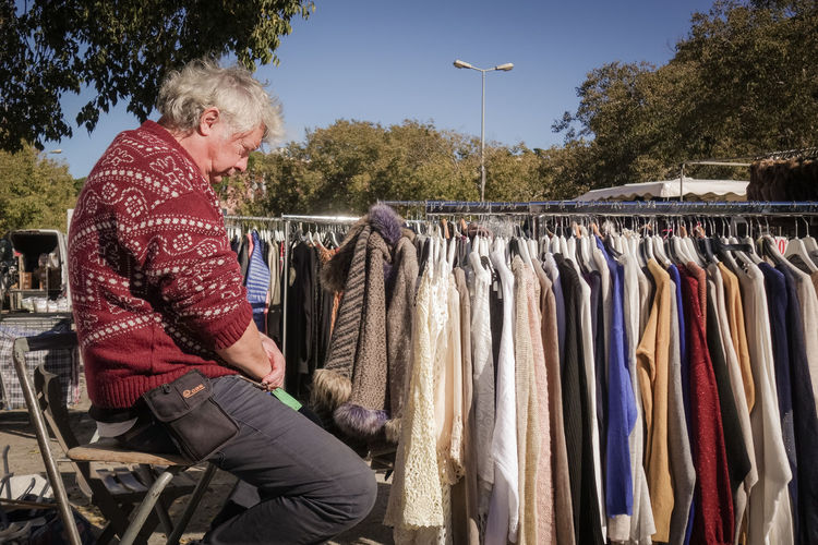 Senior man sitting by rack of clothes at flea market