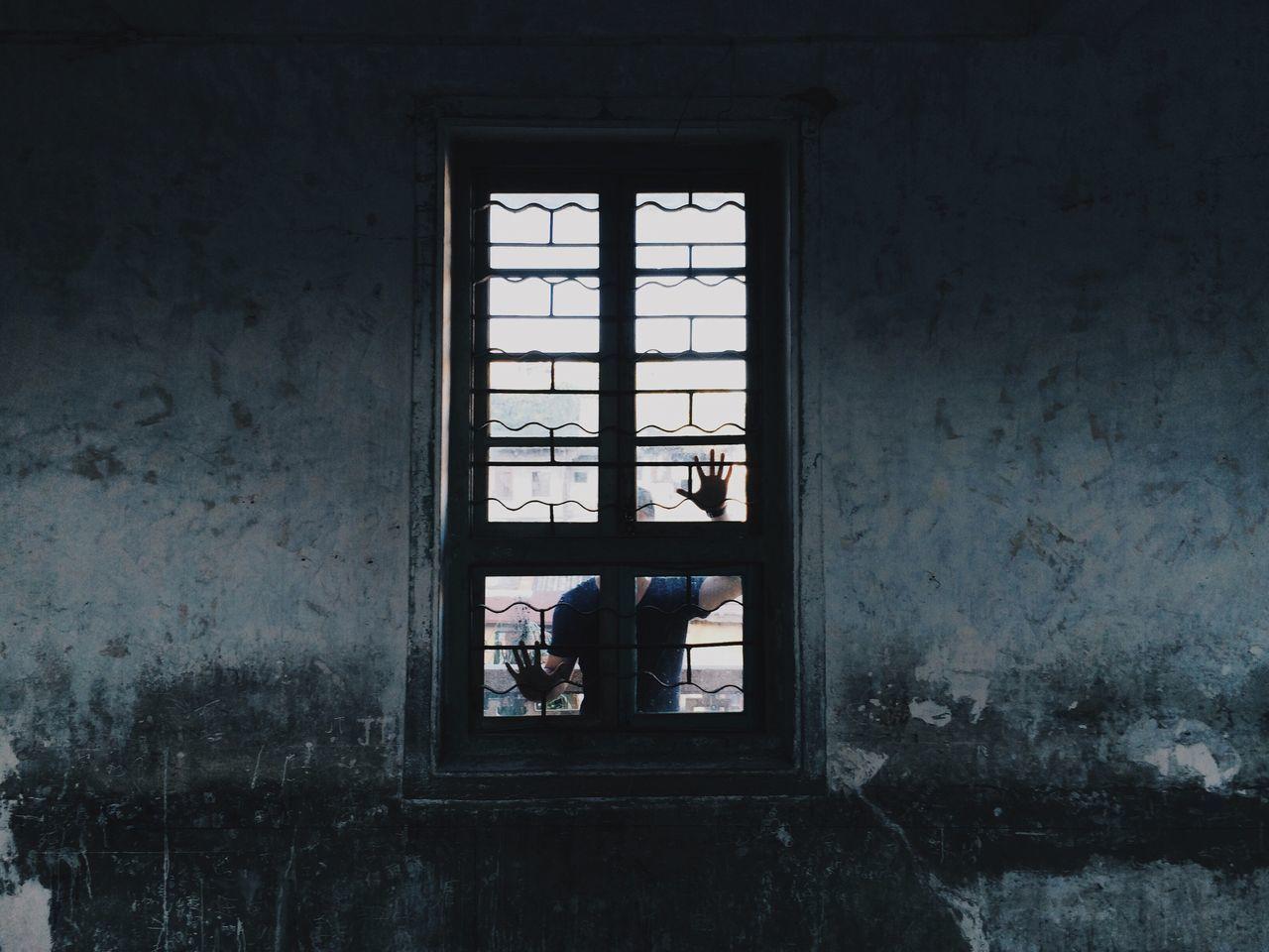 Man standing behind closed window