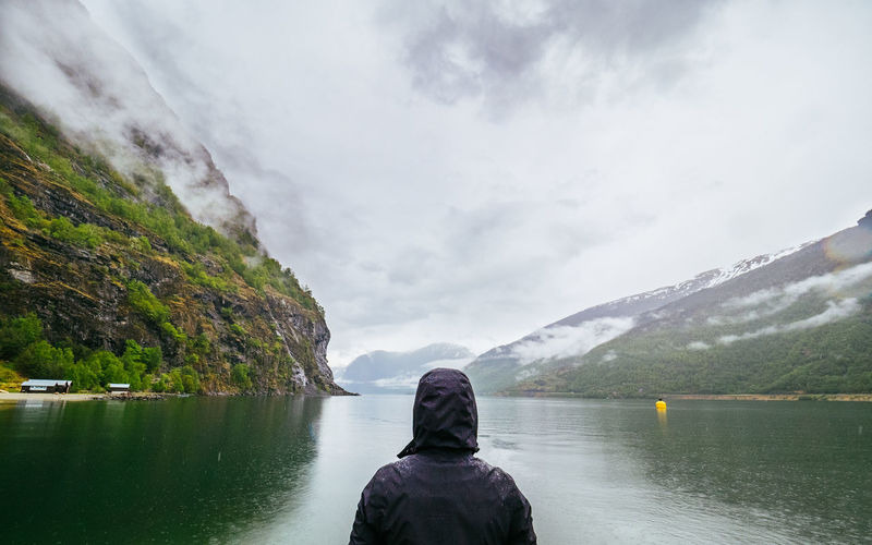 Adult Adventure Beauty In Nature Cloud - Sky Day Epic Fjord Leisure Activity Mountain Nature Norway One Man Only One Person Outdoors People Rain Real People Rear View Relaxation Scandinavia Scenics Sky Tranquility Water Wet