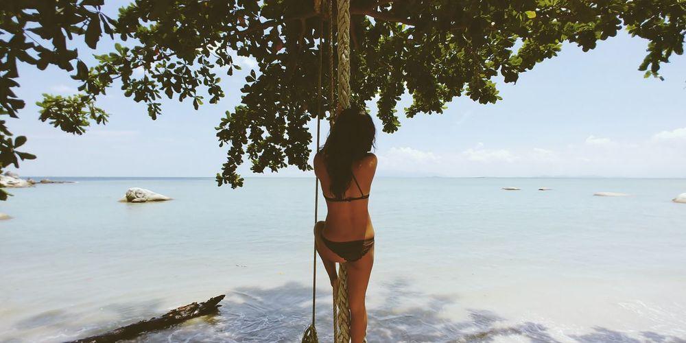 Rear view of woman wearing bikini while hanging on rope at beach