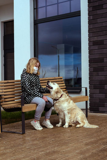 Full length of woman sitting with dog
