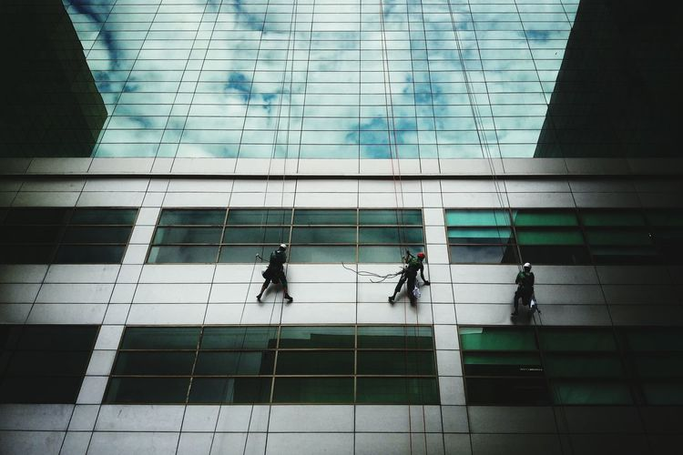 Low angle view of workers on glass building