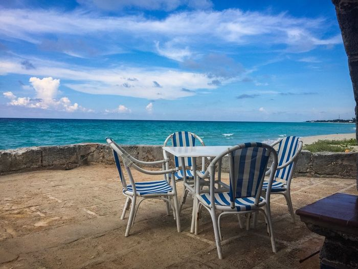 Empty Chairs And Table Against Blue Sea And Sky