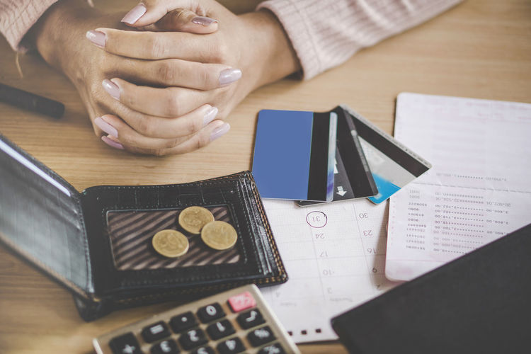 Close-up of businesswoman with hands clasped by wallet and financial items at desk