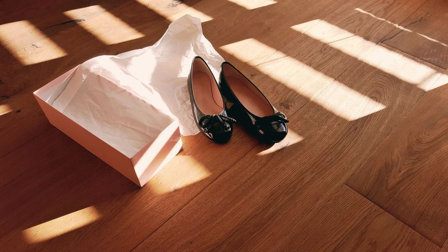 High angle view of black shoes on hardwood floor