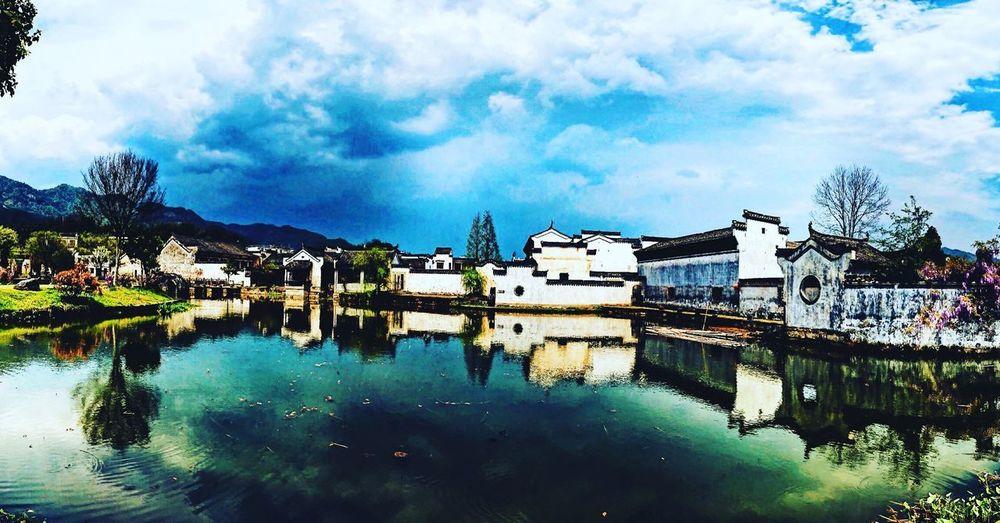 Buildings by river against sky in town