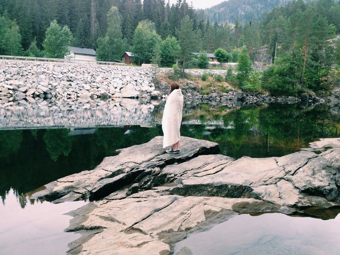 Rear view of woman standing on rock at river