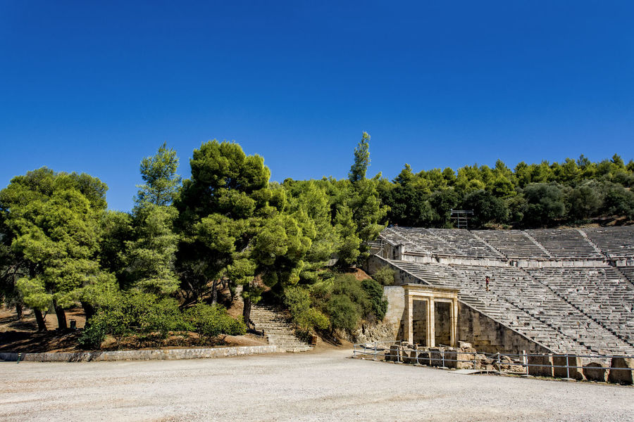 amphie theatre epidaurus Amphie Theatre Antique Architecture Blue Built Structure Clear Sky Day Epidaurus; Argolida; Peloponnese; Greece; Ancient; Culture; Theatre; Summer; Theater; Argolis; Epidavros; Background; Landscape; Architecture; Antique; Stone; Classic; Classical; Stage; Panoramic; Marble; Greek; Ruin; Steps; Stairs; Amphitheater Growth Landscape Nature No People No People, Old Buildings Outdoors Sky Stones Tree