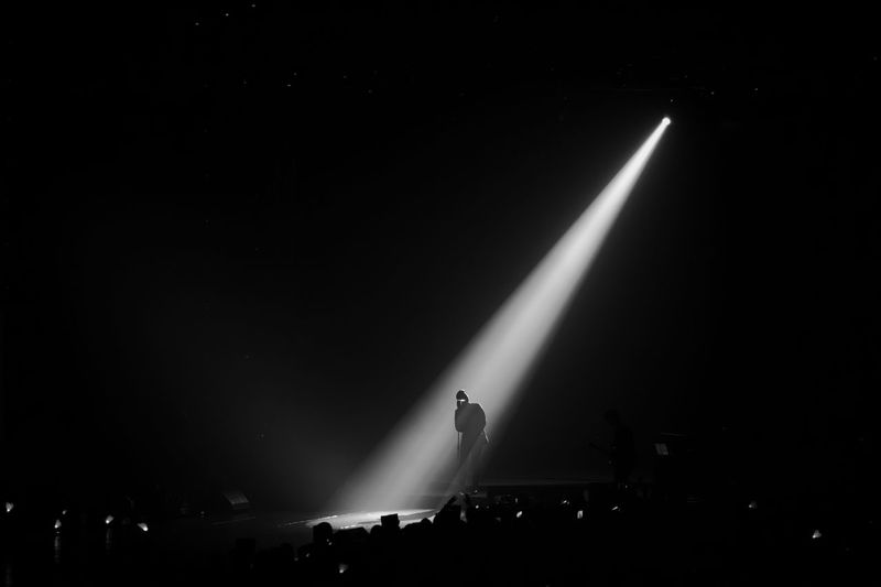 Silhouette singer singing while standing on stage at night