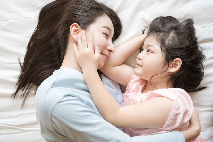 Mother and her daughter child girl hugging and Stroking her mom in the bedroom .Happy Asian family Asian  Family Happiness Happy Happy People Family Time Home House Daughter Parent Father Mother Dad Mom Love Lifestyles Living Room ASIA Japanese  Korean Thai Taiwan Bedroom Bed Kiss Smiling Smile Fun Portrait Girls Hug Hugging Embracing moments of happiness Morning Wake Wakeup Wake Up