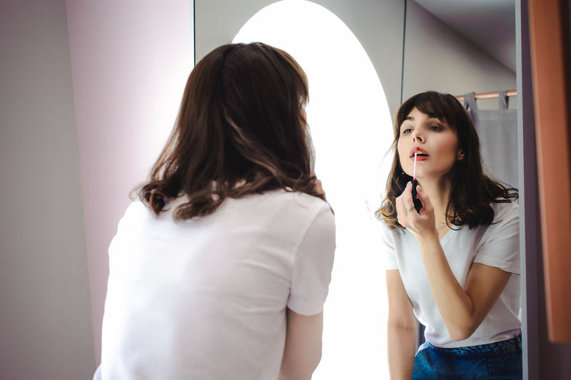 Portrait of a beautiful woman, dyes her lips lipstick pink, looking in the mirror Casual Clothing Day Indoors  Lifestyles Mirror Real People Reflection Standing Young Adult Young Women