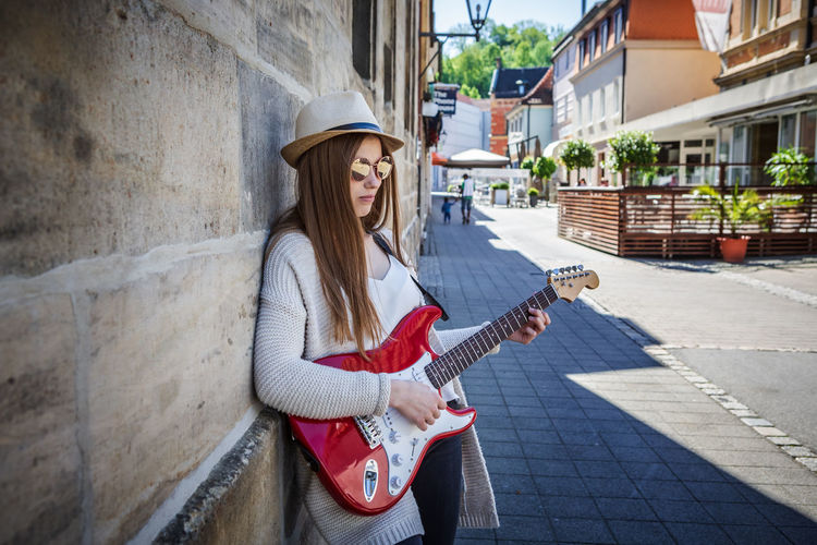 Young woman playing guitar while standing by wall