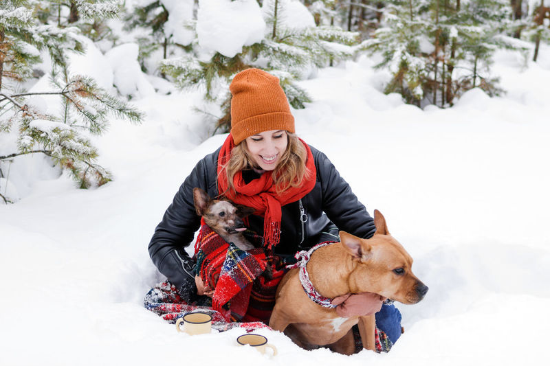Portrait of woman with her two dogs wrapped in red checkered plaid on a snow in forest.
