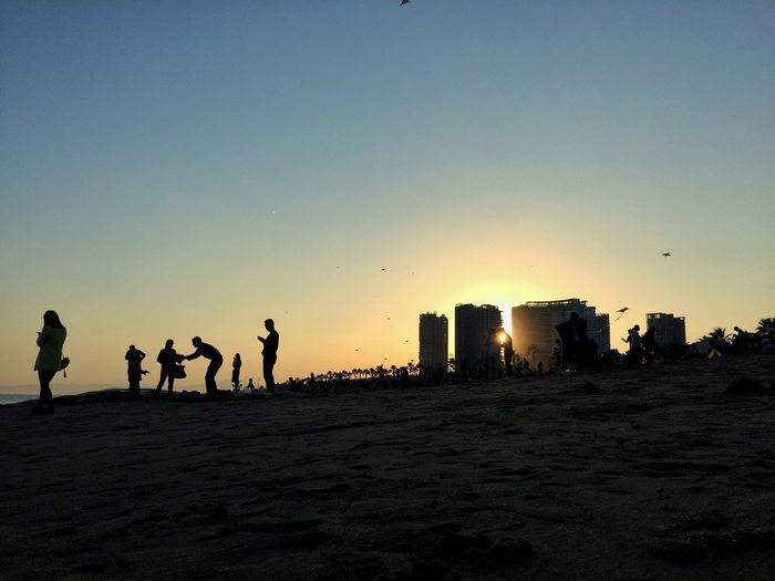 Silhouette of people standing on beach
