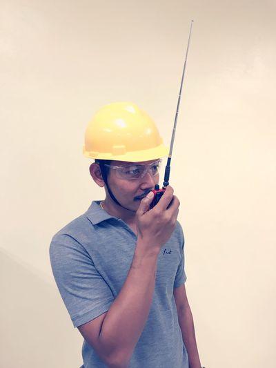 Engineer talking with walkie talkie against wall