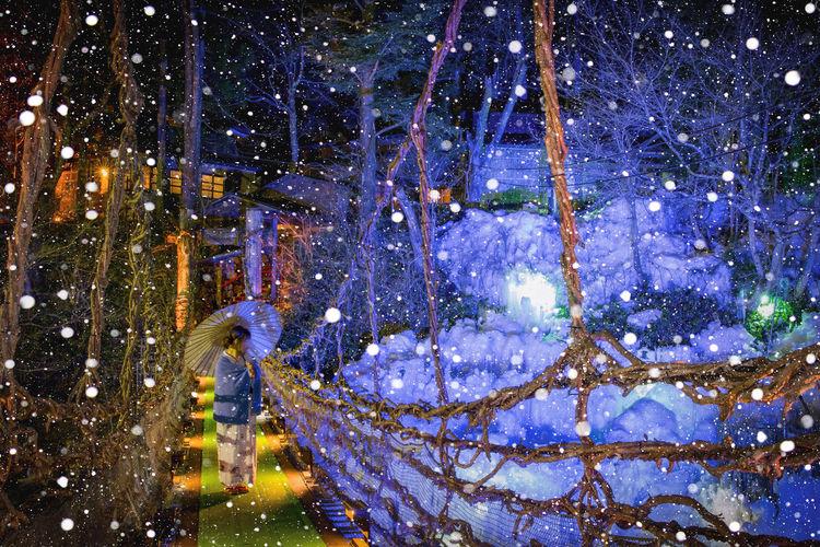 Woman standing on footbridge during snowfall at night