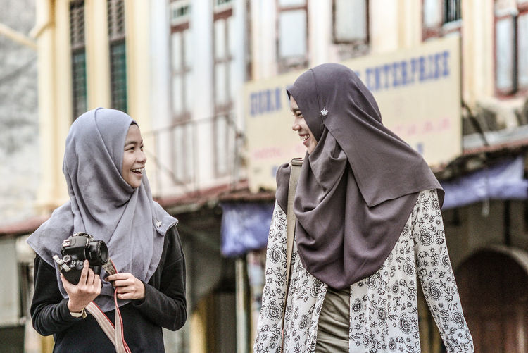 Happy Friends Wearing Hijab Talking Against Building In City
