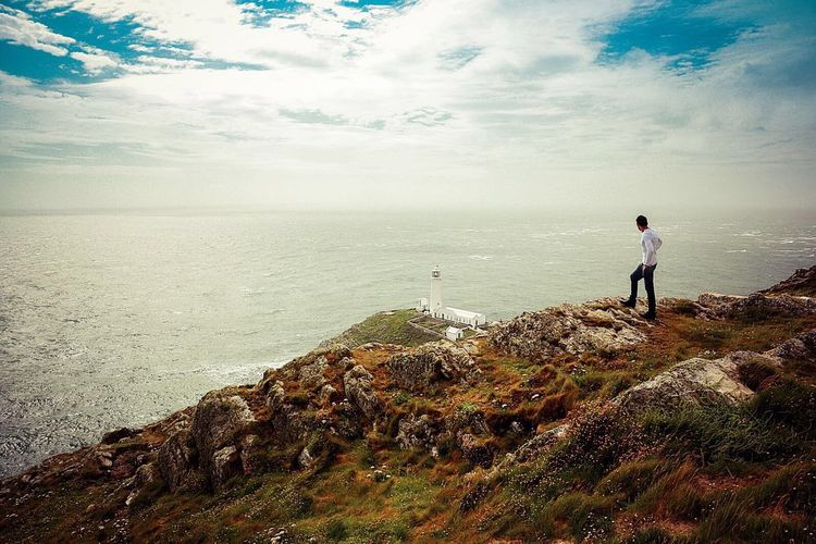 Man standing on mountain by sea against sky