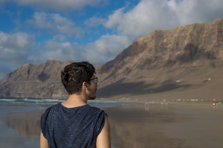 Rear view of young man looking at mountains against sky