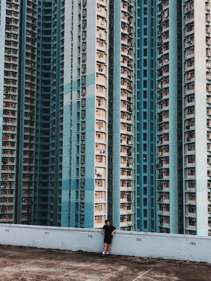 FULL LENGTH OF MAN STANDING AGAINST OFFICE BUILDINGS
