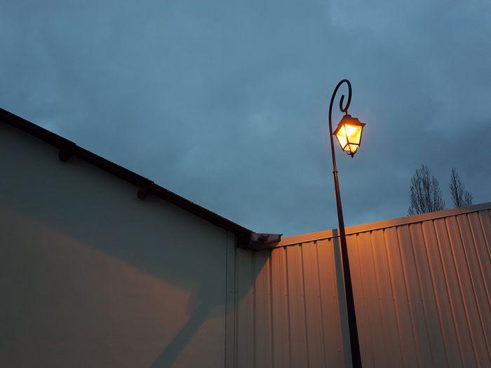 Illuminated electric lamp against sky