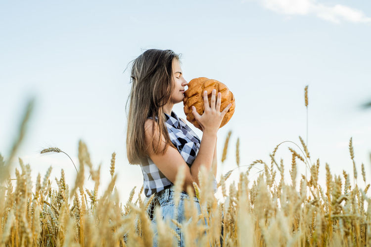 Teenager girl holding loaf of bread while standing amidst farm
