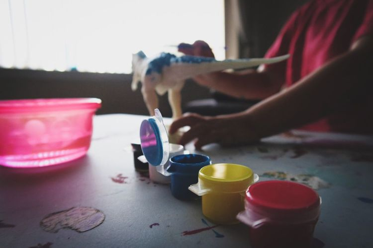 Midsection Of Girl Coloring Origami On Table At Home