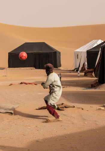 Moroccan Man Real People Full Length One Person Casual Clothing Lifestyles Leisure Activity Men Land Sand Sky Day Nature Built Structure Architecture Males  Outdoors Desert Building Exterior Mid Adult Climate Arid Climate Sahara Desert Tent Camp Morocco Soccer Soccer Ball Dunes Sand Dune Sand Dunes