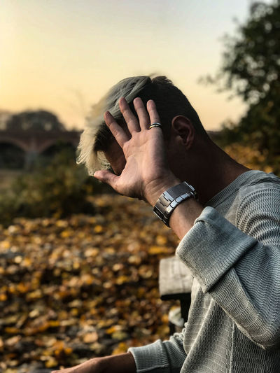Side view of young man hiding face with hand while sitting outdoors