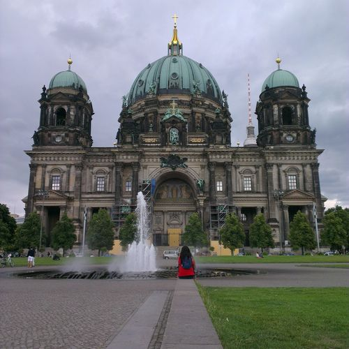 Rear view of woman sitting against berlin cathedral