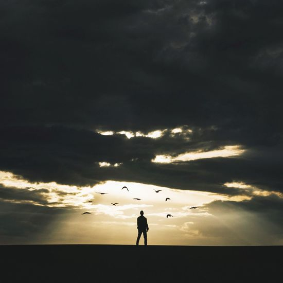 Silhouette man standing on landscape against clouds