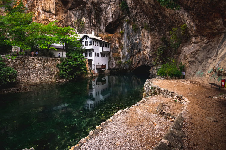 River amidst buildings against mountain