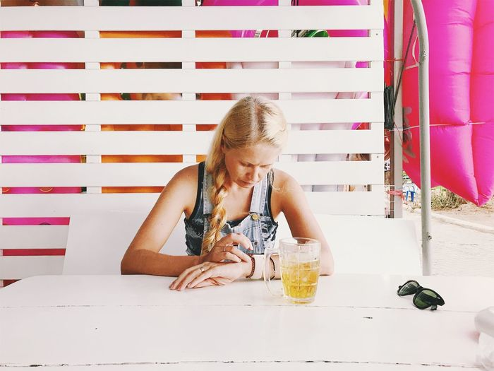 Woman Checking Time While Sitting At Table In Restaurant