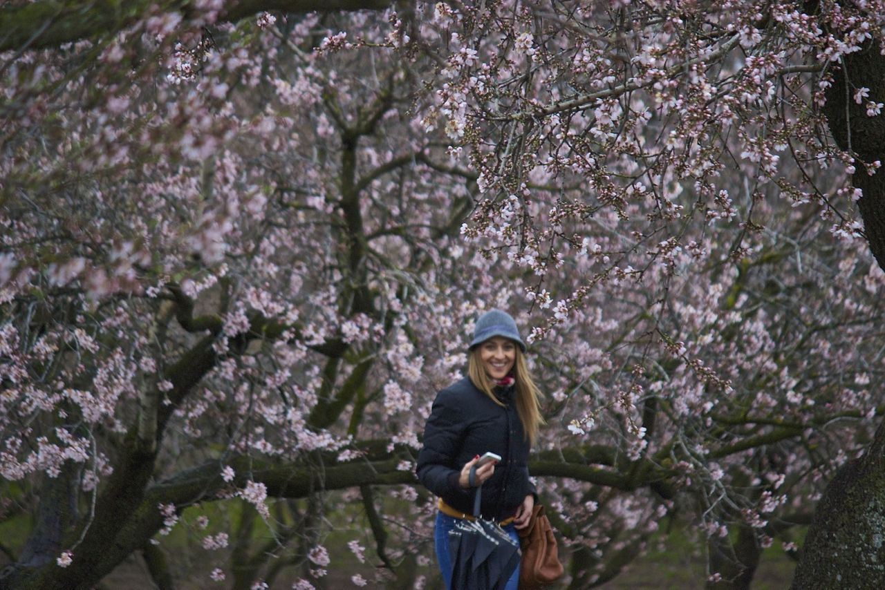 tree, flower, springtime, blossom, branch, nature, one person, beauty in nature, growth, leisure activity, front view, outdoors, freshness, standing, fragility, day, low angle view, cap, real people, tree trunk, young adult, climbing, adult, people