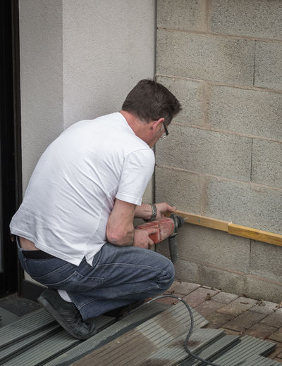 Man Drilling Wood On Wall At Home
