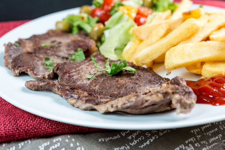 Close-up of beef with french fries in plate