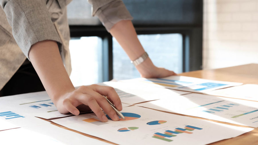 Midsection of businesswoman analyzing graph on desk in office