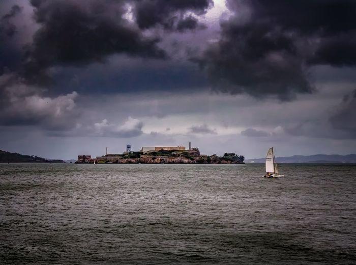 Lone sailboat in calm sea against clouds
