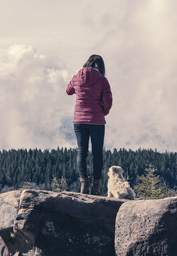 Rear view of woman with dog standing on rock against sky