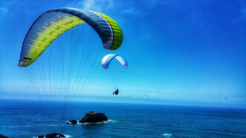 Adventure & Extreme Sport. Paragliding over ocean. Blue Yellow Gray Extreme Sports Adventure Thrill Sport Cliff Jumping Ocean Zen Background Dual Two Merging Copy Space Converge Timeless Paragliding Parachute Extreme Sports Sea Water Adventure Flying Beach Blue Mid-air Gliding Horizon Over Water Kite