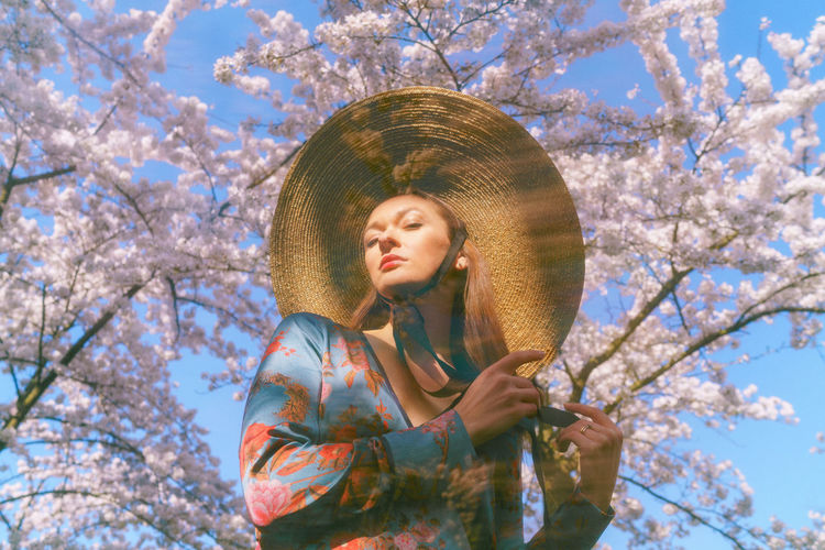 Portrait of young woman standing by cherry tree against sky