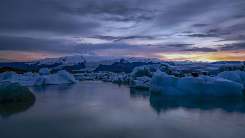 Jökulsárlón is a glacial lagoon, bordering Vatnajökull National Park in southeastern Iceland. Its still, blue waters are dotted with icebergs from the surrounding Breiðamerkurjökull Glacier, part of larger Vatnajökull Glacier. The Glacier Lagoon flows through a short waterway into the Atlantic Ocean, leaving chunks of ice on a black sand beach. Water Cloud - Sky Sky Scenics - Nature Ice Tranquility Beauty In Nature Tranquil Scene Glacier Cold Temperature Environment No People Reflection Waterfront Winter Sunset Nature Frozen Lake Iceberg Floating On Water Jökulsárlón Dusk Global Warming Iceland