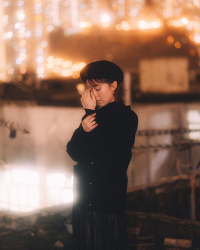Young woman looking at illuminated camera at night