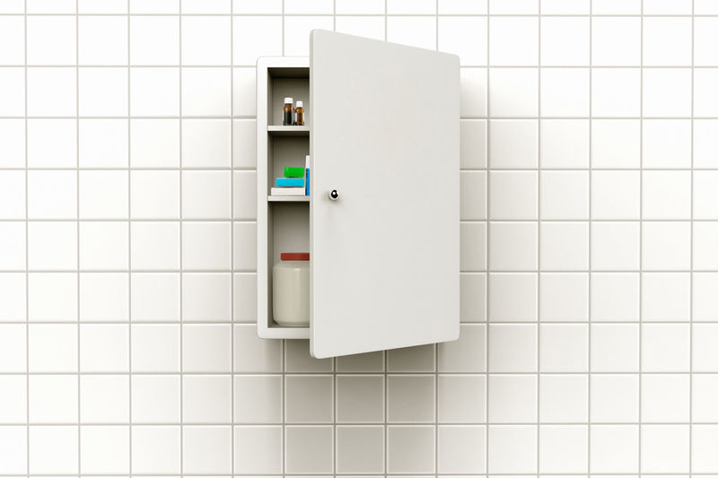 Close-up of cabinet on tiled wall in bathroom
