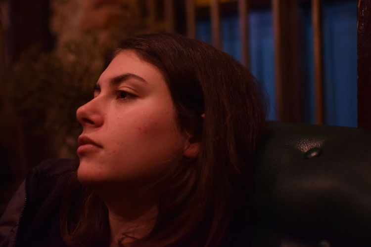 Close-up of thoughtful young woman on sofa at home