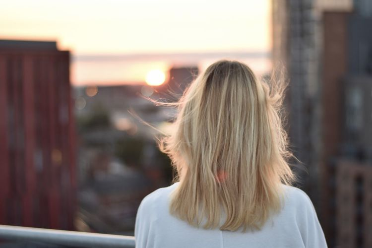 Rear view of a woman looking out at the city
