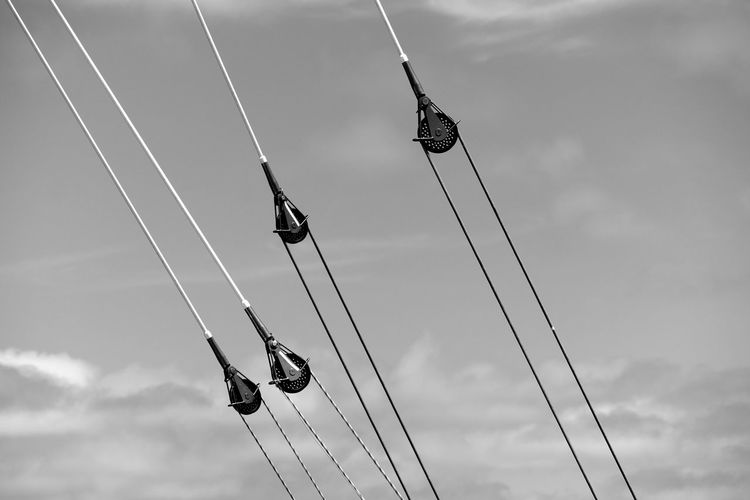 Low angle view of pulleys against sky