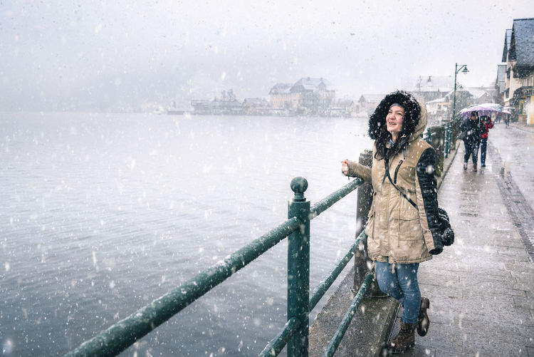 Winter joy theme image with a young woman laughing and enjoying the snowfall, on the Hallstatter See shore, in the famous Hallstatt town, in Austria. Austrian Alps Winter Scene Casual Clothing Cold Temperature Day Frozen Full Length Hallstatt Hallstatt, Austria Hallstattersee Happiness Leisure Activity Nature One Person Outdoors Real People Smiling Snow Snowing Warm Clothing Water Weather Winter Young Adult Young Women